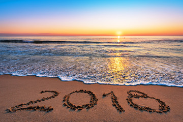 New Year 2018 is coming concept. 2018 written on sandy beach