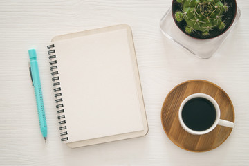 top view of open notebook with blank pages next to cup of coffee on white background. ready for adding text or mockup