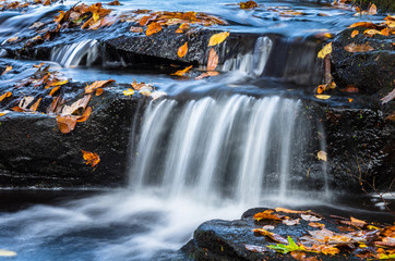 Close View of Small Waterfall in Autumn with Fallen Leaves on the Wet Rocks. Southford Falls Provincial Park, CT.