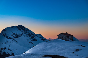 Photo sur Aluminium Pleine lune View of a shelter in the snow covered Vardousia mountains in Greece at sunset