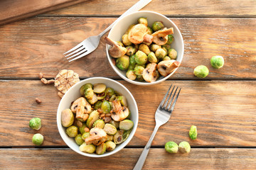Bowls with yummy brussel sprouts salad on wooden table