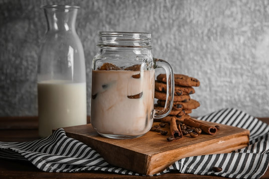 Mason jar with delicious iced coffee on wooden board