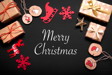 New year's background on a black desk decorated with toys, presents, Santa Claus, snowman. Bright colored background symbolizes the new year celebration. Great useful template to wright words down.