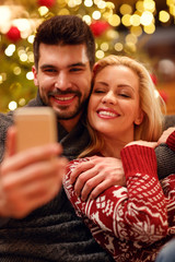 lovely couple in warm sweaters taking selfie picture with smartphone at home.