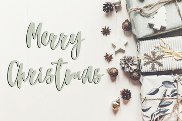 merry christmas text, seasonal greetings card sign. stylish modern presents with ornaments cones anise on  rustic white wooden background top view. xmas flat lay