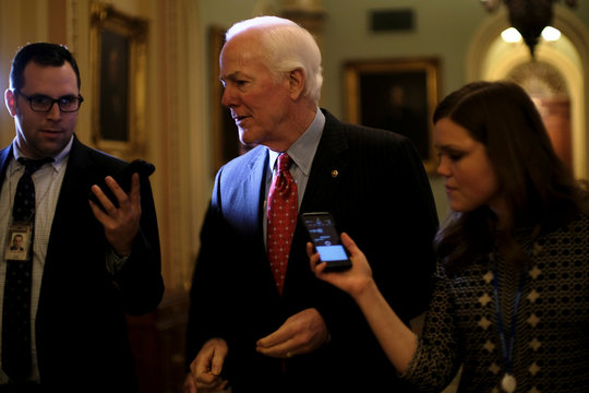 U.S. Senate Majority Whip Cornyn speaks to reporters on his way to the Senate floor during debate over the Republican tax reform plan in Washington
