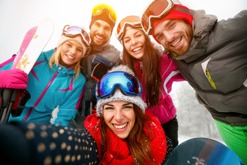 happy friends having fun on winter hodays. Snowbarders and skiers group team making selfie
