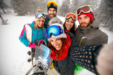 smiling friends having fun on winter hodays. Snowbarders and skiers group team making selfie