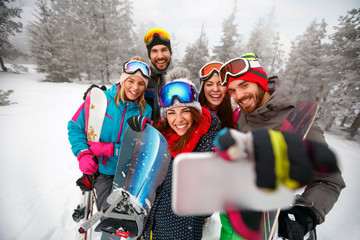 smiling friends with ski on winter holidays - Skiers having fun on the snow