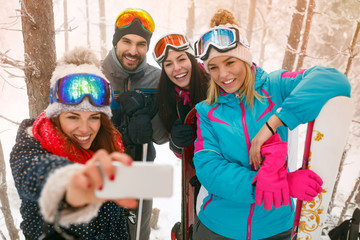 snowboarders or skiers making selfie in fog forest