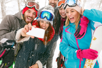 young snowboarders or skiers making selfie in fog forest