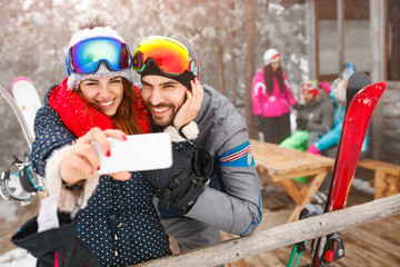 cheerful couple taking selfie together with cell phone in snowy mountain