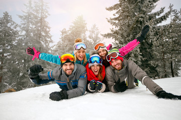 friends on winter holidays - Skiers lying on snow and having fun