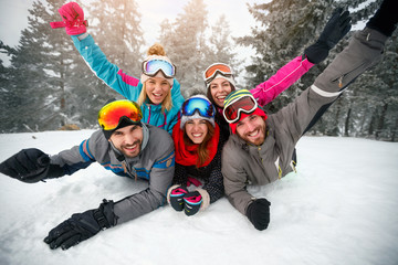 Skiers lying on snow and having fun