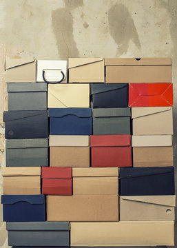 A stack of folded cardboard boxes from under the shoes stands against the background of a shabby wall.