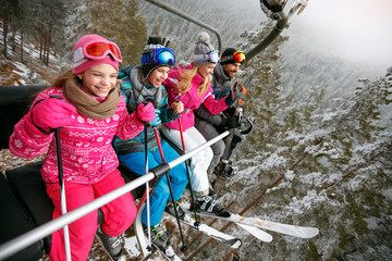 Skiing, ski lift, ski resort - happy family skiers on ski lift