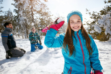smiling girl playing on snow at ski holiday in mountains