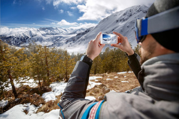 Hiker man taking photographs mountain landscape with smartphone