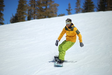 Positive snowboard photo, bright colors, sunny day, winter, white snow. Yellow jacket, green pants. Smile, good mood