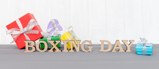 Gift boxes is tied with a ribbon with words BOXING DAY on wood white background