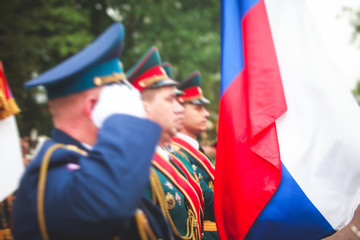 "A formation line of russian army officers with flags, banners and orchestra in military formation in uniform with chevron ""Russian Armed Forces"", line up during the victory parade"