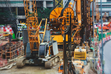 A large construction site in the city, the process of massive buliding construction with heavy vehicle at work, excavator, elevating crane and bulldozer