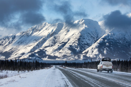A car driving towards mountains on the Alaska Highway