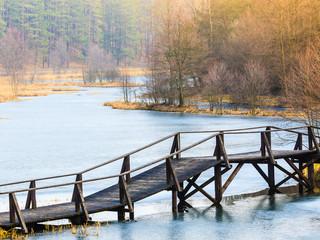 Old, wooden, small bridge on frozen lake