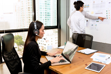 Future  woman business leader concept. Young Asian  business woman teleconferencing in front of laptop with two white men in background brainstorming.