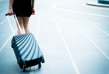 Young business traveller concept. Young business woman with black roller suit case in urban city taken outdoor.