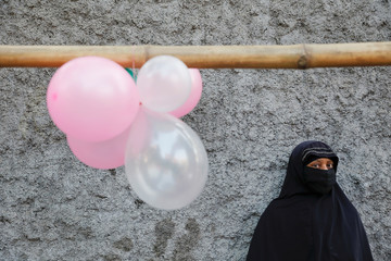 A woman stands under balloons decorating an alley near the Holy Rosary church before Pope Francis arrives there, in Dhaka