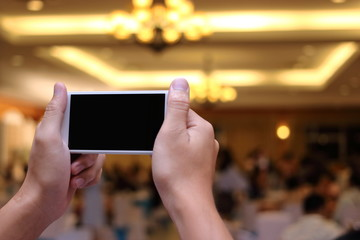 Hands of unidentified people taking photo of dinner party with mobile smart phone with blank screen