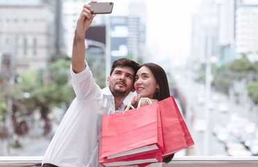 Happy couple taking selfie with mobile phone after a hard day of huge sale shopping in asian country.