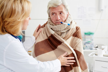 Sick mature man with thermoteter in his mouth listening to doctor advice in clinics
