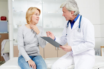 Female patient complaining to doctor about sore throat and other symptoms of flu