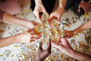 Several flutes with sparkling champagne in hands of intercultural friends during toast