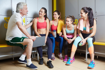 Successful girls listening to their trainer advice during break after workout