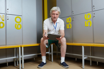 Mature trainer with clipboard sitting on bench in sports dressing room and looking at camera