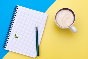 Top view on blank notebook with pen and cup of coffee, separated on yellow and blue paper background.