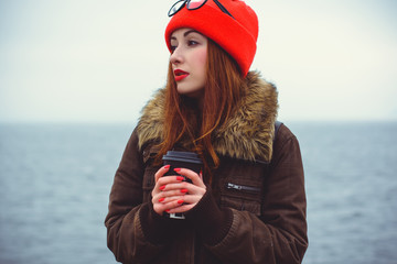 Melancholic teen hipster with depression mood. Lifestyle young people or student. Girl with cup of coffee in London cold weather