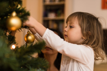 Little girl hanging christmas ball on a tree