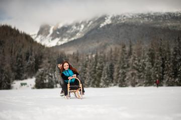 Couple sledding on snowy mountains