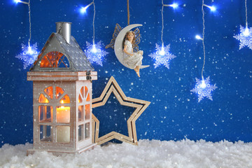Old wooden lantern, snowflakes silver garland light, fairy on the moon over the snow and blue background.