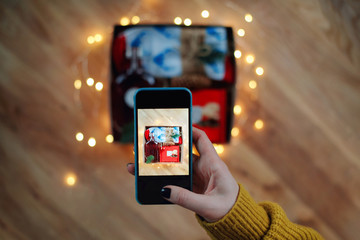 Woman taking photo of Christmas gift box with smartphone. Instagram photography blogging workshop concept. A girl hanging a phone taking a photo of present on wooden table.