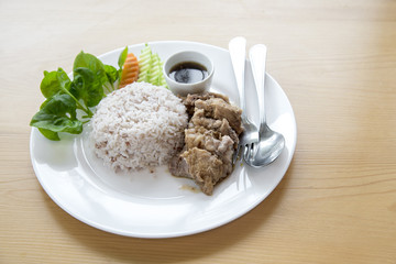 Steamed rice with stew pork in sauce and fresh vegetable side dish. this  is thai food.