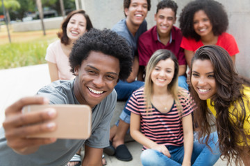Large group of international young adults taking selfie with phone