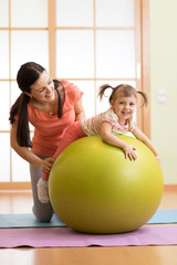 Mother with childdoing exercises with gymnastic ball at home. Concept of caring for the baby's health.