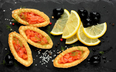 Delicious appetizer of smoked salmon with lemon, olives, salt and pepper on a black plate