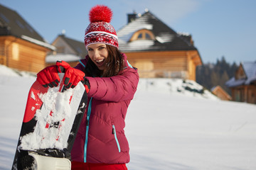Sport woman  snowboarder on snow over winter resort