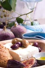 Fetakäse mit Oliven, Olivenöl und Feigen auf einem Tellr mit Besteck und einem Glas im Hintergrund